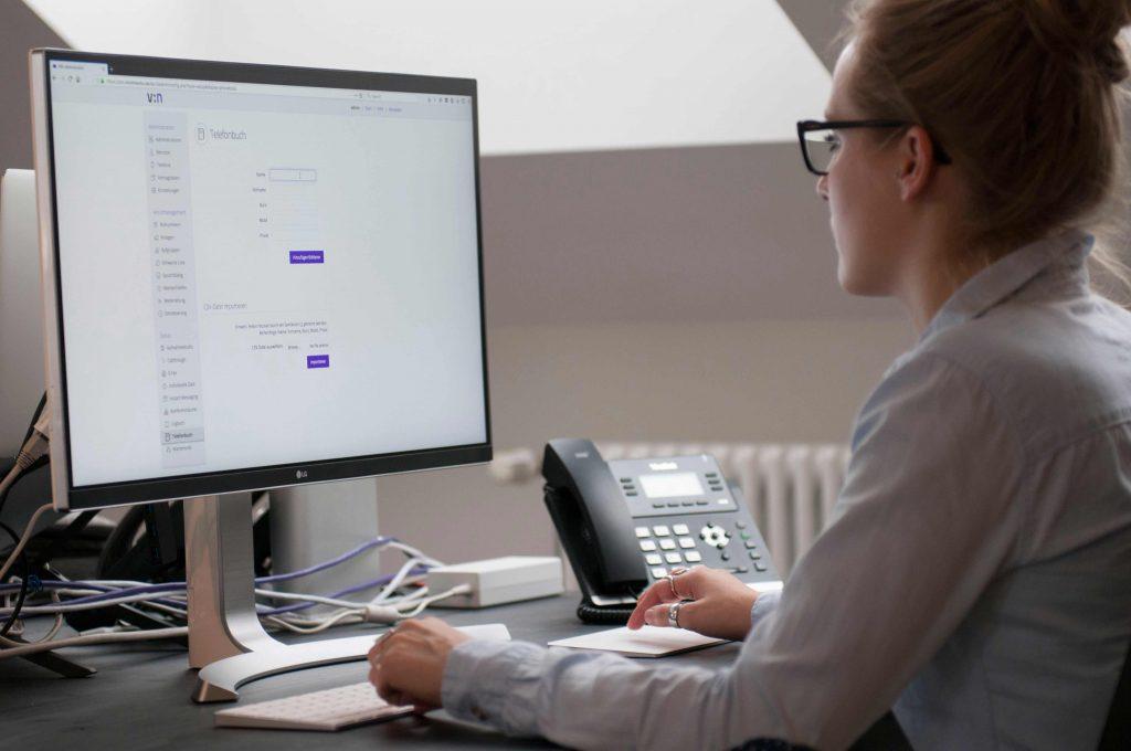 Bild einer Mitarbeiterin am Arbeitsplatz, während sie die Telefonanlage konfiguriert.