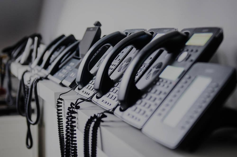 Bild verschiedener Tischtelefone in Reihe auf einer Ablage